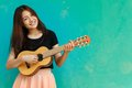 Beautiful asian girl playing guitar a thai is in front of a blue wall background Royalty Free Stock Image