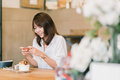 Beautiful Asian girl taking photo of sweet desserts at coffee shop, using smartphone camera, posting on social media Royalty Free Stock Photo