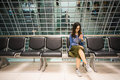 Beautiful asian girl using smartphone, waiting to board airplane, conceptual Royalty Free Stock Photo