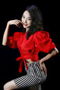 Beautiful asian girl wearing black and white striped skirt and red clothes isolated on black background Royalty Free Stock Photography