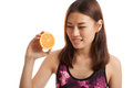 Beautiful Asian healthy girl with orange fruit licks her lips. Royalty Free Stock Photo