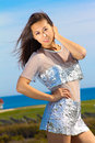 Beautiful asian model in a silver dress of descent posing by the ocean orion aam Royalty Free Stock Photo