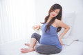 Beautiful asian pregnant woman frowning while holding her back,