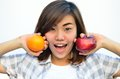 Beautiful asian teenage holding orange and apple fruits near smi Stock Images