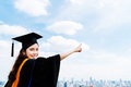 Beautiful asian university or college graduate student woman in graduation academic dress or gown, smiling and pointing at copy sp Royalty Free Stock Photo