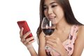 Beautiful asian woman chat on phone and drink red wine isolated white background Stock Photography