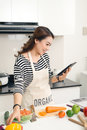 Beautiful asian woman cooking according to recipe on tablet scre