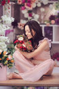 Beautiful asian woman florist in pink dress with bouquet of flowers in hands in flower store Royalty Free Stock Photo