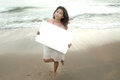 Beautiful asian woman holding a white billboard on the beach . Stock Image