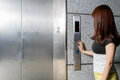 Woman Standing by Elevator pressing button Royalty Free Stock Photo