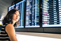 Beautiful Asian woman traveler at flight information screen in an airport, travel or time concept Royalty Free Stock Photo