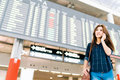 Beautiful Asian woman traveler on mobile phone call at flight information board in airport, holiday vacation travel concept Royalty Free Stock Photo