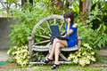 Beautiful asian woman using computer notebook in blue dress in garden Royalty Free Stock Photography