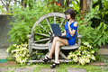 Beautiful asian woman using computer notebook in blue dress in garden Royalty Free Stock Photos