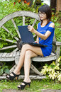 Beautiful asian woman using computer notebook in blue dress in garden Stock Photo