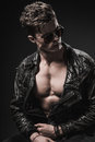 Beautiful athletic bodybuilder male model posing in studio. Expression on camera. Brutal man in leather suit. Royalty Free Stock Photo