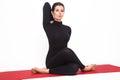 Beautiful athletic girl in black suit doing yoga. gomukhasana asana - pose cow's head. Isolated on white background. Royalty Free Stock Photo