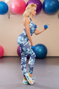 Beautiful athletic girl doing exercise in the fitness room. Sport woman in sportswear workout