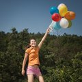 Beautiful and athletic girl jumping with balloons on a green meadow this image has attached release Stock Photos