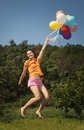 Beautiful and athletic girl jumping with balloons on a green meadow this image has attached release Royalty Free Stock Photography