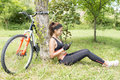 Beautiful athletic woman with bike using tablet computer, outdoo Royalty Free Stock Photo
