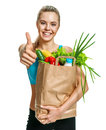 Beautiful athletic woman gesturing thumb up with grocery bag full of healthy fruits and vegetables Royalty Free Stock Photo
