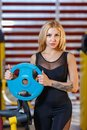 Athletic woman holds a blue pancake in the gym.