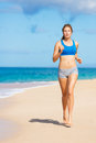 Beautiful Athletic Woman Running on the Beach Stock Photo