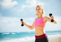 Beautiful athletic young woman exercising working out outdoors at the beach Stock Image