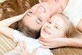 Beautiful attractive mother or sister with child girl lying face to face happy smiling looking at camera women closeup portrait Royalty Free Stock Photo