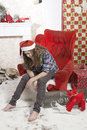 Beautiful attractive sad disappointed brown haired girl in santa hat sitting in the chair near fir tree and heap of presents in Royalty Free Stock Photo