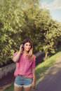 Beautiful and attractive woman moving her her aside wearing sexy casual denim shorts with macrame lace edge attachment a pink Stock Image