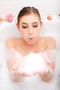 Beautiful attractive young woman in a bath having spa fun with foam in hands blowing away closeup image portrait Royalty Free Stock Photos