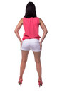 Beautiful, attractive young woman in blouse and short shorts with an elegant figure, buttocks, ass, standing backwards Royalty Free Stock Photo