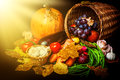 Beautiful autumn harvest of vegetables and leaves on black background with sun light Royalty Free Stock Images