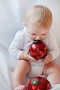 Beautiful baby boy playing with Christmas tree balls Stock Image