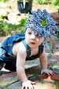 Beautiful baby crawling on in an outside garden dressed in denim overall and a huge flower hair band on her head Royalty Free Stock Photos