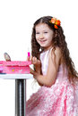 Beautiful baby girl doing makeup and lipstick in a dress isolated on a white background Royalty Free Stock Photo