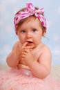 Beautiful baby girl months studio portrait of with fingers in her mouth Royalty Free Stock Image