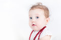 Beautiful baby girl with a red necklace Royalty Free Stock Photo