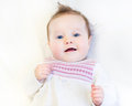 Beautiful baby girl in a warm knitted pink dress on white blanket Stock Image
