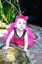 Beautiful baby with pink bow crawling in an outside garden on rock bright and tutu Royalty Free Stock Photos