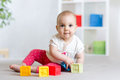 Beautiful baby plays cubes on the floor and smiling girl Royalty Free Stock Photography