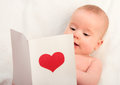Beautiful  baby and postcard  Valentine's Day with a red heart Stock Photography