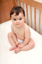 Beautiful baby sitting in cot Royalty Free Stock Images