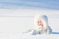 Beautiful baby in a white suit sitting in a snow field Royalty Free Stock Photo
