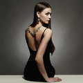 Beautiful back of young woman in a black sexy dress beauty girl with a necklace on her back luxury brunette Royalty Free Stock Photos