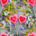 Beautiful background of flowers field of daisies and bells and two hearts made of caramel and marzipan on Valentine`s day. Copy Royalty Free Stock Photo
