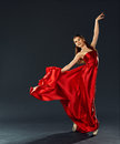 Beautiful ballerina dancing a long red dress flying and in pointe Stock Photo