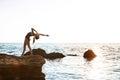 Beautiful ballerina dancing, posing on rock at beach, sea background.